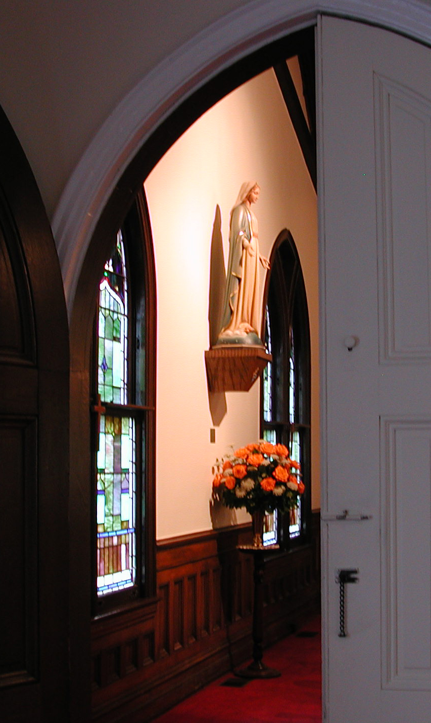 Flowers under statue of Mary